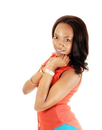 long shot: Un colpo mezzo di lunghezza di una bella ragazza nera per sfondo bianco, le mani underher shin, in una camicia arancione e lunghi capelli neri Archivio Fotografico