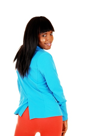 A pretty African American woman standing with the back to the cameraand looking over her shoulder, in blue jacket and red tights, over white  photo