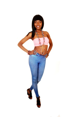 A tall slim young black woman standing for white background in blue tightsand a pink top with a long necklace, smiling  photo