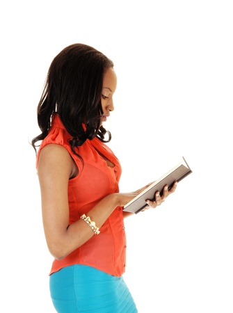 A lovely black woman standing for white background in a orange blouseand reading a book  photo