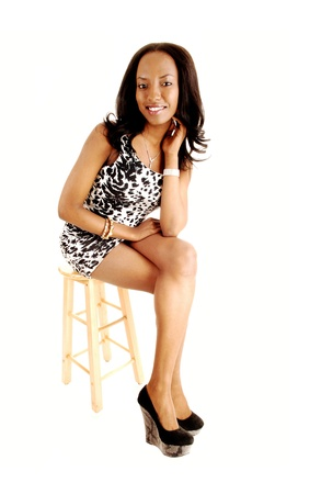 chairs: A beautiful young black woman in a black and white dress and long blackhair sitting on a chair for white background and smiling