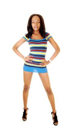 legs spread: Una mujer joven encantadora y muy alto en un corto vestido colorido fondo standingfor blanco en el estudio con sus largas piernas se extendi� Foto de archivo