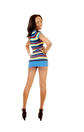 A nice tall and young black woman standing in a colorful short dressfrom the back, looking over her shoulder, for white background  Stock Photo