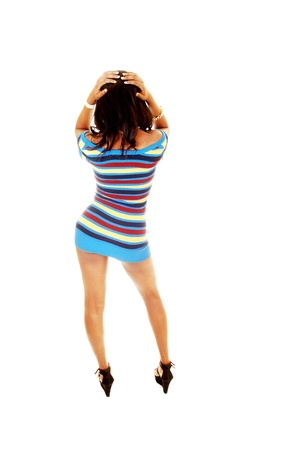 A very tall young black woman standing from the back for white backgroundwith her hands on her head and pushing out her hip Stock Photo - 16796865
