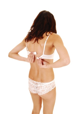 A young slim woman in white lace lingerie standing from the back is closingher bra, with her long brunette hair for white background  photo