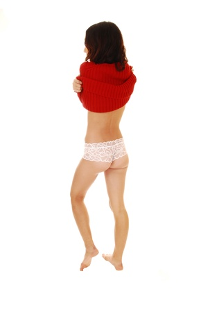 A young woman in white lace panties standing for white background andtaking of her red sweater, bare feet from the back