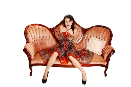 vintage furniture: A pretty woman in a colorful long dress sitting on a antique pink sofa, lookinginto the camera for white background  Stock Photo