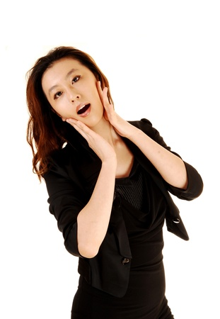 A lovely slim Asian woman in a black dress standing for white backgroundholding her hands on her face and is very surprised  photo