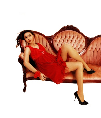 A young and pretty Asian woman in a red dress lying on a pink antic sofafor white background and looking into the camera  photo