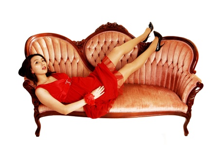 A young and pretty Asian woman in a red dress lying on a pink antic sofafor white background with her legs up  photo