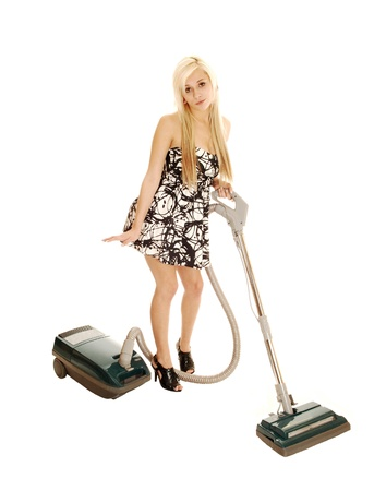 A young pretty woman standing for white background with a vacuumcleaner, in a dress and long blond hair and high heels, cleaning the house  photo