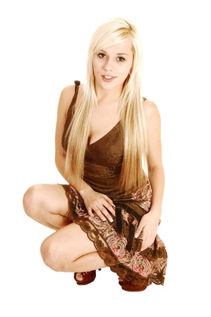 crouched: A young teenager with long blond hair crouching on the floor in a browndress for white background, looking into the camera