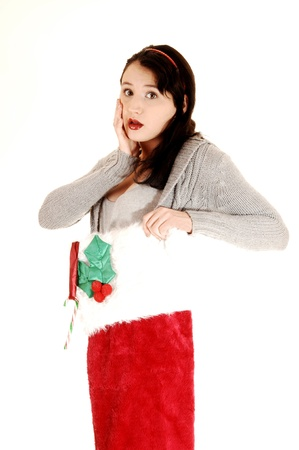 A very pretty young woman in a Christmas stocking and a Santa Claus hatholding her hand on her face, for white background Stock Photo - 17277186