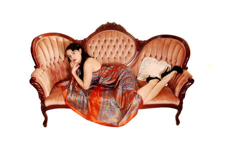 A pretty woman in a colorful long dress lying on a antique pink sofa onher stomach, looking into the camera for white background  photo