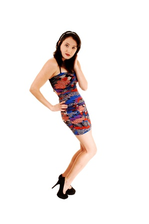 sidewards: A pretty and slim young woman standing sidewards in a colorful dress and high heels for white background.