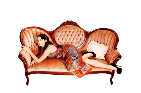 vintage furniture: A pretty woman in a colorful long dress lying on a antique pink sofa on her side, looking away for white background.