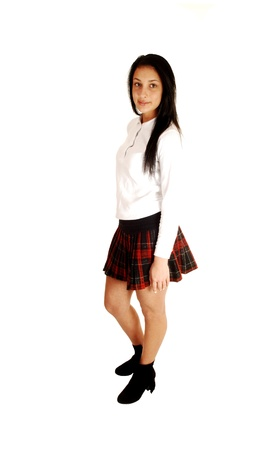 A teenage girl standing for white background in her school uniformwith her long black hair  photo