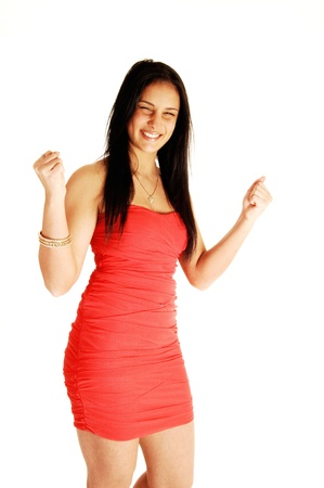 A beautiful and very excited young teenage girl standing in a red dressfor white background, with her long black hair  Stock Photo