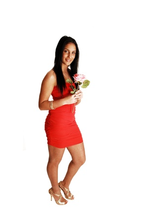 A pretty teenager girl in a red strapless dress and gold high heels standingin the studio for white background, holding a pink rose  Stock Photo - 17602550
