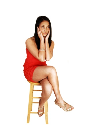 A young teen girl with a seus expression, in a red strapless dress sittingon a chair for white background, with gold colored high heels on  Stock Photo - 17602552