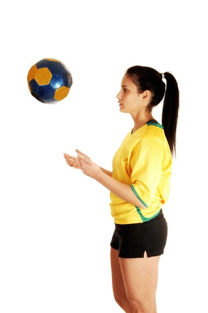 A pretty teenage girl standing in the studio in her soccer uniform andplaying with the football, her hair in a ponytail for white background Stock Photo - 17602553