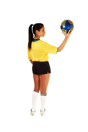 A teenage girl standing from the back, in a soccer uniform and holding theball up, with her long black hair in a ponytail for white background Stock Photo - 17602548