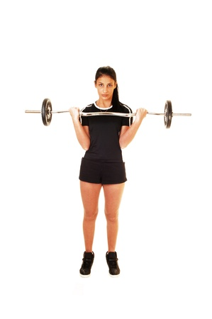 A teenager girl in a black top and shorts standing for white backgroundlifting weight to exercise her body  Stock Photo - 17602546