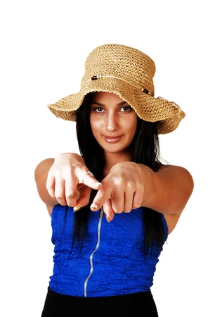 A teenager girl in a blue corset, black skirt and a straw hat standing forwhite background with her long black hair, pointing with both fingers atthe photographer  Stock Photo - 17602561