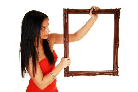 A lovely young teen girl in a red dress holding up a picture frame, in a reddress and black hair standing in the studio for white background Stock Photo - 17748169