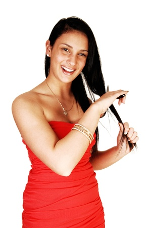 A beautiful teen girl with a scissor in her hand, smiling and cutting her nicelong black hair, for white background Stock Photo - 17748159