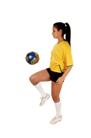 A pretty teenage girl standing in the studio in her soccer uniform andplaying with the football, her hair in a ponytail for white background