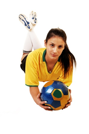 A young pretty soccer girl lying on the floor in her uniform, yellow top and blackshorts, with a soccer ball in her hand for white background