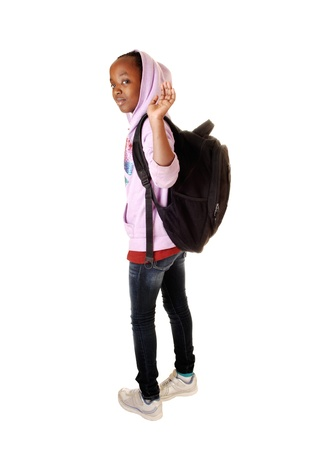 A black teen school girl waving goodbye and leaving for school with her blackbackpack on her back for white background  photo