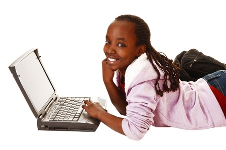 A young pretty black teen girl lying on the floor with her laptopsmiling into the camera, for white background  photo