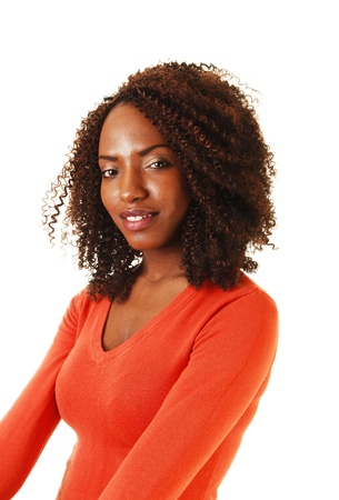A portrait of a beautiful African American teenager, sitting with her long curlybrown hair, in a orange sweater, for white background