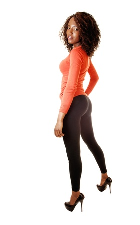 A tall and slim black teenager girl in a orange sweater and black tightsstanding in the studio for white background