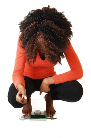 A lovely black teen girl crouching on a scale, looking on her little weight,for white background in an orange sweater and black tights  photo