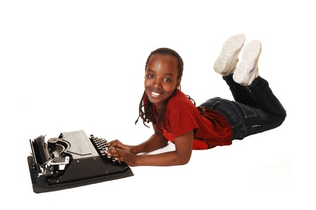 A black teen girl lying on the floor in jeans, smiling into the camera andtrying to write on an old typewriter, for white background  photo
