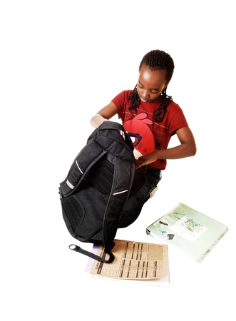 A young black school girl looking into her school backpack, kneeling onthe floor and some books lying outside, for white background  photo