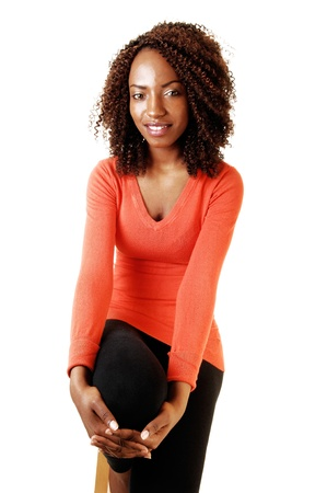 A very tall young teenage girl sitting on a chair in a orange sweater andblack tights, smiling, for white background  Stock Photo