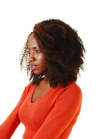 visage femme africaine: Un portrait d'une belle adolescente afro-am�ricaine, assis avec ses cheveux curlybrown longtemps, dans un chandail orange, pour fond blanc Banque d'images