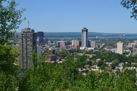 The view of downtown Hamilton with some high rises and a park in theforeground, and the lake Ontario in the background, from the mountain