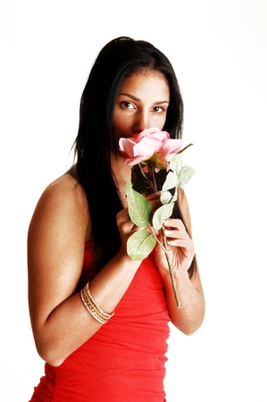 A pretty teenager girl in a red strapless dress standingin the studio for white background, holding a pink rose Stock Photo - 18630441