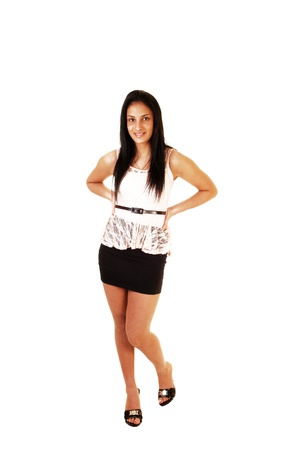 short cut: A slim teenager girl standing for white background,wearing a short black skirt and white blouse and high heels  Stock Photo
