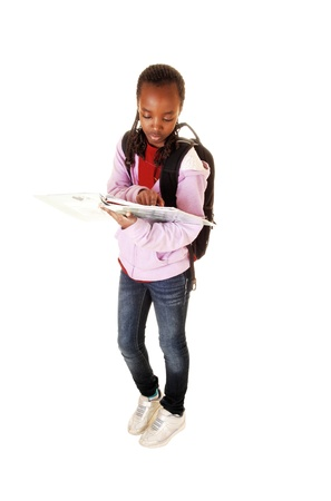 A young black teen girl standing for white background with her backpack onher back, reading in one of her school books