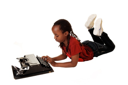 A black teen girl lying on the floor in jeans, typingand on an old typewriter, for white background  photo
