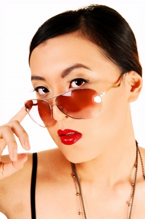 A closeup shoot of a classy young chinese woman looking over her sunglasses for white background  photo