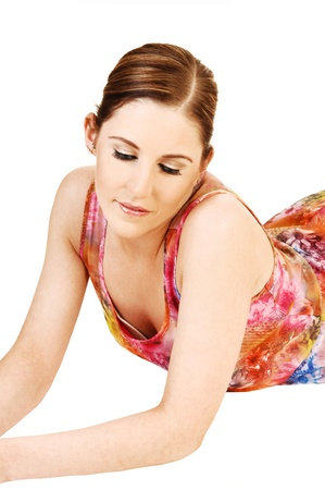 A portrait shoot of a young pretty woman, lying on her stomach on the floor for white background, in a colourful dress and looking down  photo
