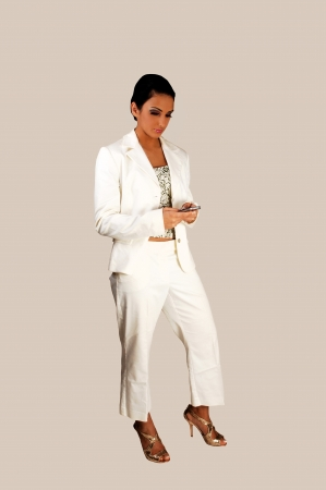 A young pretty business woman in a white suit standing for light graybackground, texting on her cell phone  photo