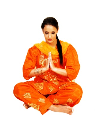 A beautiful young east indian teen girl sitting on the floor in her nicetraditional indian orange dress, holding her hands together and praying, for white background  photo